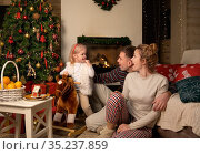 Family celebrates Christmas by the fireplace and Christmas tree. Стоковое фото, фотограф Алексей Кузнецов / Фотобанк Лори