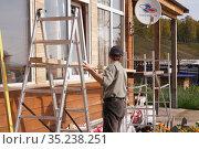 Рабочий устанавливает строительные леса для ремонта деревянного дома на улице в солнечный осенний день (2019 год). Редакционное фото, фотограф Светлана Попова / Фотобанк Лори