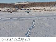 Следы человека ведут на сельский берег по замерзшей заснеженной поверхности Большого озера. Стоковое фото, фотограф Светлана Попова / Фотобанк Лори