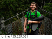 Photographer Fabian Mühlberger, on bridge during journey to Walami, Yushan National Park, Taiwan. March 2019. Photographing for Wild Wonders of Taiwan. Стоковое фото, фотограф Fabian Muhlberger / Wild Wonders of China / Nature Picture Library / Фотобанк Лори