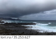 Gran Canaria, view towards the main body of the island from El Confital beach on the edge of Las Palmas de Gran Canaria, rain sweeping through the island. Редакционное фото, фотограф Tamara Kulikova / Фотобанк Лори