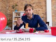Caucasian man making video call sitting a table eating spaghetti. Стоковое фото, агентство Wavebreak Media / Фотобанк Лори