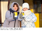 Friendly looking women holds disposable cups of coffee, suggests to drink together, focus is on paper cups. Стоковое фото, фотограф Кекяляйнен Андрей / Фотобанк Лори
