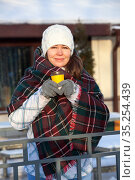 Petty smiling woman drinks hot coffee from yellow paper cup wrapping with red checkered woollen scarf, winter time, urban street. Стоковое фото, фотограф Кекяляйнен Андрей / Фотобанк Лори