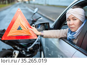 Woman a driver showing triangle emergency sign while sitting in car after road accident with motorcycle, does not leave the car. Стоковое фото, фотограф Кекяляйнен Андрей / Фотобанк Лори