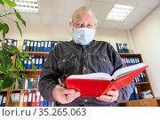 Mature male archivist holding open red notebook in hands, looking at camera, man wearing face mask due Covid-19 pandemic. Стоковое фото, фотограф Кекяляйнен Андрей / Фотобанк Лори