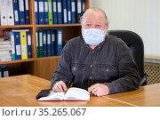 Senior business man wearing face mask sitting at the table in office room due Covid-19 flu. Стоковое фото, фотограф Кекяляйнен Андрей / Фотобанк Лори
