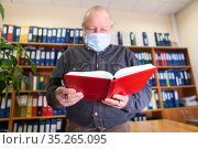 Senior male archivist holding open red notebook in hands, looking at camera, man wearing face mask due Covid-19 pandemic. Стоковое фото, фотограф Кекяляйнен Андрей / Фотобанк Лори