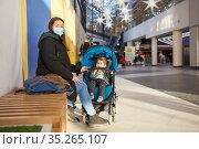 Mother resting with her child sitting in children pram, family walking in shopping center, adult woman wearing face mask, copyspace. Стоковое фото, фотограф Кекяляйнен Андрей / Фотобанк Лори