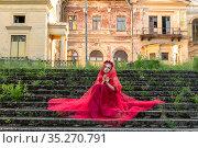 Девушка в красном платье на фоне сидит на ступенях. Стоковое фото, фотограф Литвяк Игорь / Фотобанк Лори