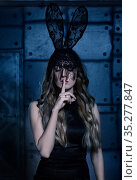 The mystery of Black Rabbit. Young woman in black rabbit fancy dress, with closed eyes and finger on lips. Стоковое фото, фотограф Serg Zastavkin / Фотобанк Лори