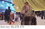 Smiling young woman in a wheelchair and her boyfriend at Christmas celebration on the streets - waving hands to the camera. Стоковое видео, видеограф Константин Шишкин / Фотобанк Лори