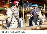 Mature couple in helmets riding by horse at barn at summer day. Стоковое фото, фотограф Яков Филимонов / Фотобанк Лори