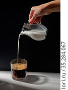 hand with jug pouring cream to glass of coffee. Стоковое фото, фотограф Syda Productions / Фотобанк Лори