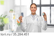 smiling female doctor holding medicine at hospital. Стоковое фото, фотограф Syda Productions / Фотобанк Лори