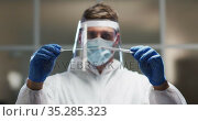 Caucasian male medical worker wearing protective clothing and face shield inspecting dna swab in lab. Стоковое видео, агентство Wavebreak Media / Фотобанк Лори