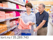 Mature couple husband and wife choose towels in supermarket. Стоковое фото, фотограф Татьяна Яцевич / Фотобанк Лори