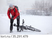 Caucasian man stands on bike lane and touching his injured knee after falling down, slippery pathway in city at winter season. Стоковое фото, фотограф Кекяляйнен Андрей / Фотобанк Лори