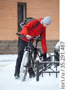 Young Caucasian man locking his bicycle to steel fence, leaving bike on the street at winter time. Стоковое фото, фотограф Кекяляйнен Андрей / Фотобанк Лори