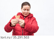Portrait of attractive woman with shape of heart in hands standing with closed eyes, red winter jacket, white background. Стоковое фото, фотограф Кекяляйнен Андрей / Фотобанк Лори