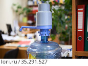 Water dispenser bottle with plastic hand pump standing in an office room. Стоковое фото, фотограф Кекяляйнен Андрей / Фотобанк Лори