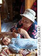 Happy senior granny looking at newborn grandchild lying on bed, holding baby hand and smiling. Стоковое фото, фотограф Кекяляйнен Андрей / Фотобанк Лори