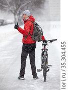 Handsome Caucasian cyclist showing thumb up while looking backward, man with his bike standing on snowy pathway at winter season. Стоковое фото, фотограф Кекяляйнен Андрей / Фотобанк Лори