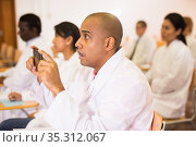 Hispanic doctor recording lecture on smartphone at refresher course. Стоковое фото, фотограф Яков Филимонов / Фотобанк Лори