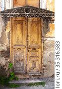 Vintage weathered wooden door under forged visor. Стоковое фото, фотограф EugeneSergeev / Фотобанк Лори