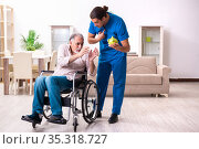 Old man in wheel-chair and young bad caregiver indoors. Стоковое фото, фотограф Elnur / Фотобанк Лори