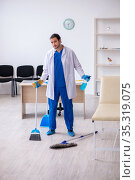 Young male contractor disinfecting clinic in pandemic concept. Стоковое фото, фотограф Elnur / Фотобанк Лори