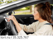 smiling woman or female driver driving car in city. Стоковое фото, фотограф Syda Productions / Фотобанк Лори