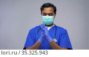 indian male doctor in uniform, mask and gloves. Стоковое видео, видеограф Syda Productions / Фотобанк Лори