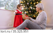 grandmother and baby girl opening christmas gift. Стоковое видео, видеограф Syda Productions / Фотобанк Лори