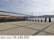 Empty outdoor cafe on Ortakoy pier square. View of Bosphorus Bridge over Bosphorus Strait, connecting Asia and Europe. Besiktas district, city of Istanbul, Turkey. Редакционное фото, фотограф Bala-Kate / Фотобанк Лори