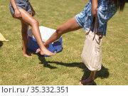 Two diverse female friends bumping legs at a pool party. Стоковое фото, агентство Wavebreak Media / Фотобанк Лори