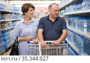 Mature couple husband and wife choose bottle of drinking water in supermarket. Стоковое фото, фотограф Татьяна Яцевич / Фотобанк Лори