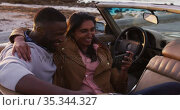 African american couple taking a selfie while sitting in the convertible car on the road. Стоковое видео, агентство Wavebreak Media / Фотобанк Лори