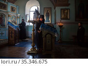 Republic of Moldova, - The first prayer in the morning in the church of Tipova Monastery at sunrise, the Pope standing by the iconostasis (2016 год). Редакционное фото, агентство Caro Photoagency / Фотобанк Лори