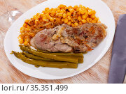 traditional spanish mutton with beans served on blue plate on wooden table. Стоковое фото, фотограф Яков Филимонов / Фотобанк Лори