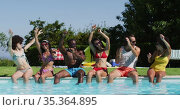 Group of diverse friends dancing and enjoying while sitting by the pool. Стоковое видео, агентство Wavebreak Media / Фотобанк Лори