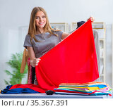 Young woman tailor working in workshop on new dress. Стоковое фото, фотограф Elnur / Фотобанк Лори