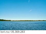 Blauer Himmel mit winzigen weißen Wolken über Ufer von See am Tag... Стоковое фото, фотограф Zoonar.com/Robert Kneschke / age Fotostock / Фотобанк Лори