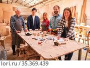Schreinerei Team mit Handwerker Meister und Azubis in der Werkstatt. Стоковое фото, фотограф Zoonar.com/Robert Kneschke / age Fotostock / Фотобанк Лори