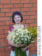 Портрет женщины средних лет с букетом полевых цветов на фоне кирпичной стены. Стоковое фото, фотограф Зобков Георгий / Фотобанк Лори