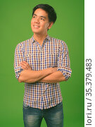 Studio shot of young handsome Filipino man against green background. Стоковое фото, фотограф Zoonar.com/Toni Rantala / easy Fotostock / Фотобанк Лори