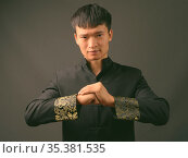 Studio shot of young Chinese man wearing traditional clothes against... Стоковое фото, фотограф Zoonar.com/Toni Rantala / easy Fotostock / Фотобанк Лори
