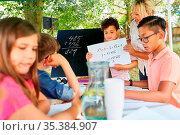 Nachhilfe Lehrerin hilft Kindern beim Rechnen im Ferienkurs der Sommerschule. Стоковое фото, фотограф Zoonar.com/Robert Kneschke / age Fotostock / Фотобанк Лори