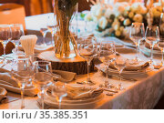 Exquisitely served table for wedding celebration. Piece of wooden... Стоковое фото, фотограф Zoonar.com/OKSANA SHUFRYCH / easy Fotostock / Фотобанк Лори