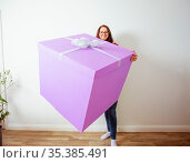 The happy girl is holding a huge violet gift box. She is standing... Стоковое фото, фотограф Zoonar.com/OKSANA SHUFRYCH / easy Fotostock / Фотобанк Лори